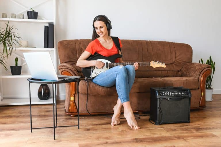 A woman learns to play electric guitar at home