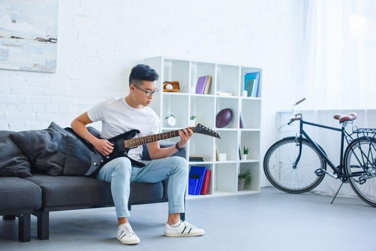 Asian man playing black electric guitar in his room