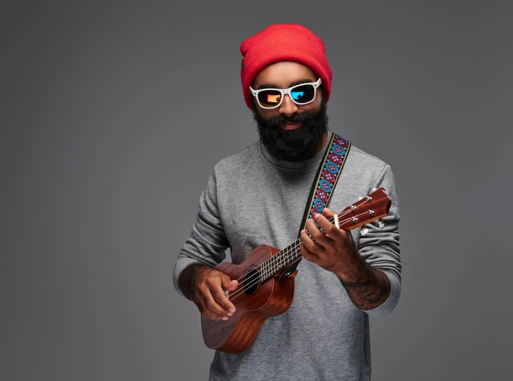 Bearded man playing ukulele with a strap