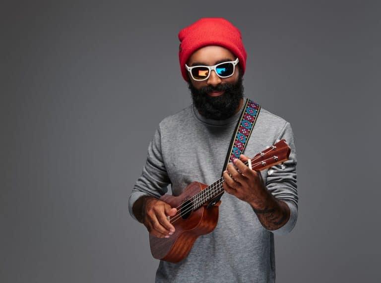 Bearded man playing ukulele with a strap