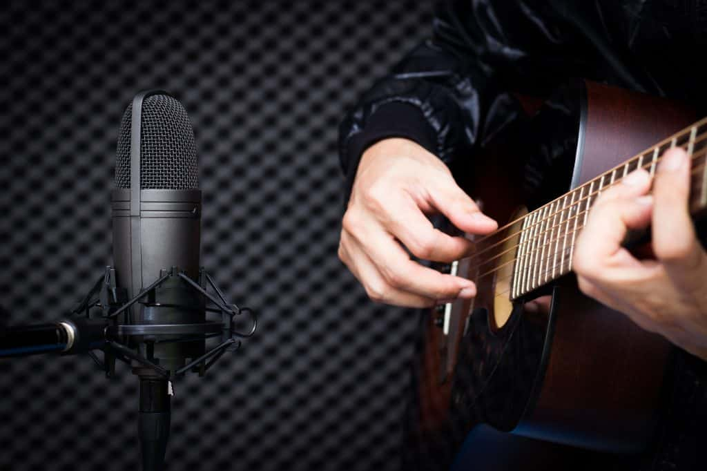 Condenser microphone recording acoustic guitar in studio