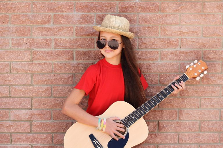 Girl in a red shirt plays on a half size guitar