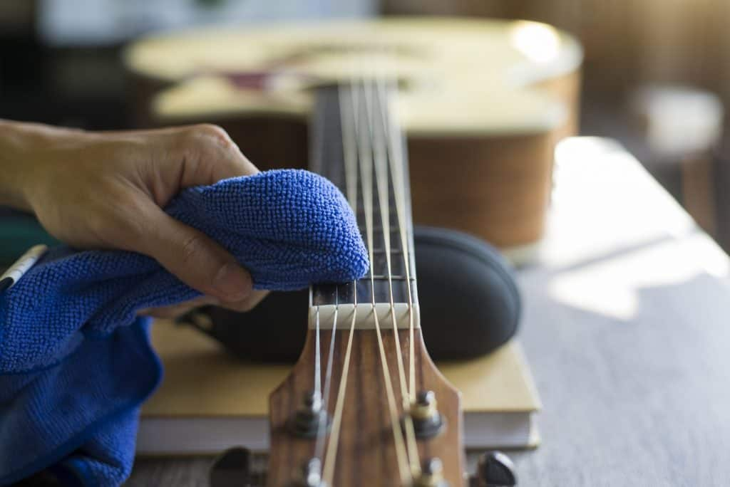 Guitar repairer is cleaning acoustic guitar strings