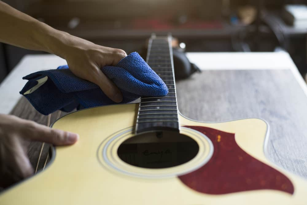 Guitar repairer is cleaning acoustic guitar strings with a cloth