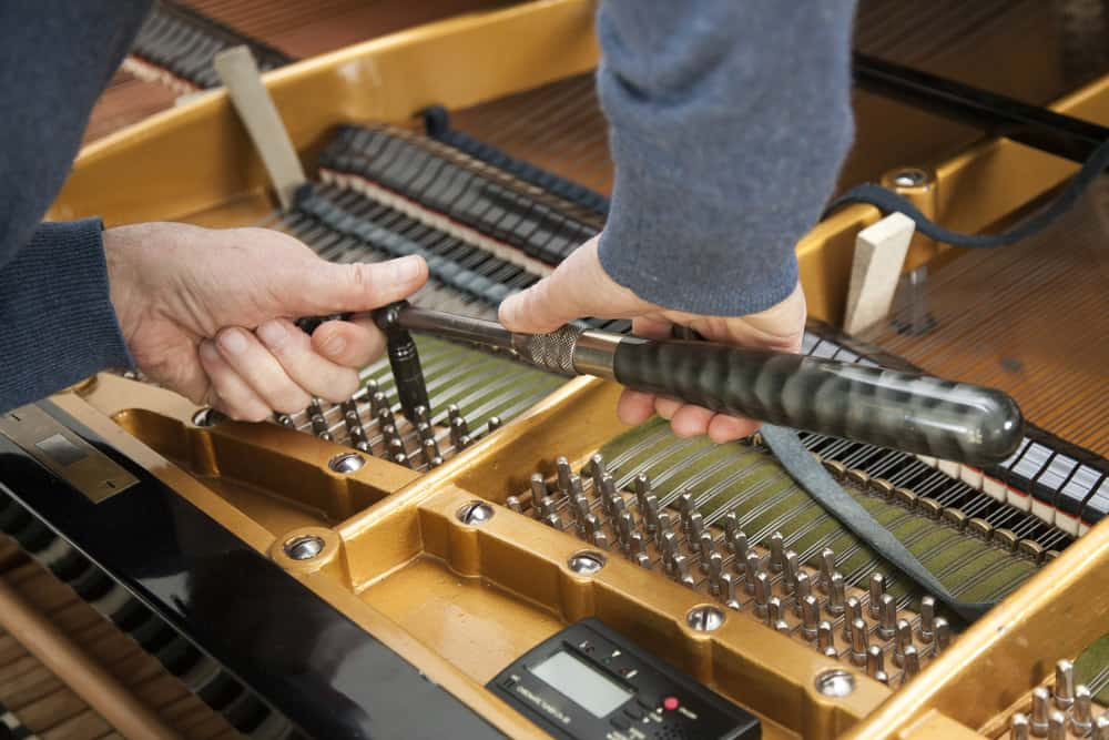 Hand and tools of tuner working on grand piano