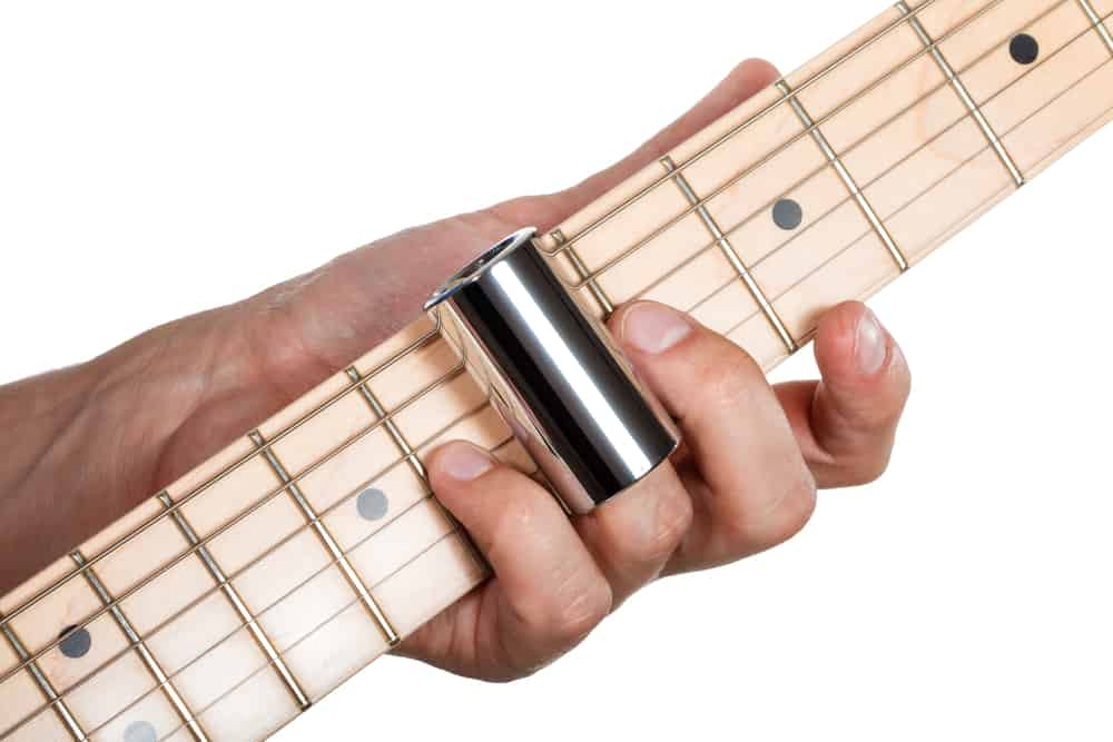 Hands of man playing electric guitar with a slide