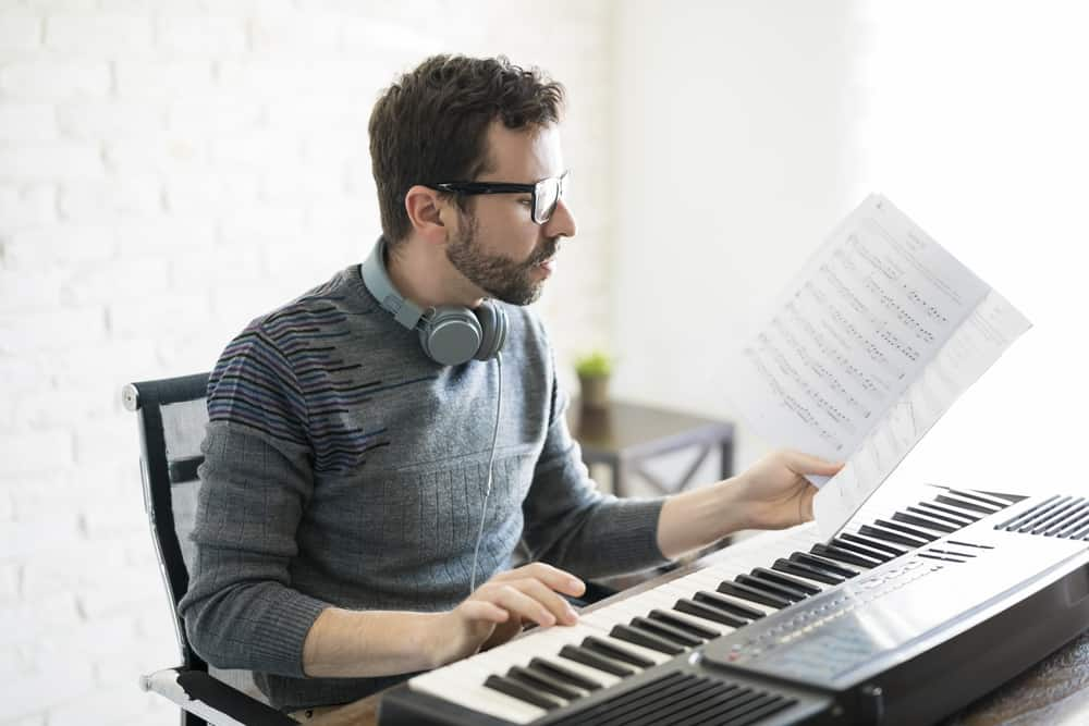Handsome young man reading music sheet while playing piano