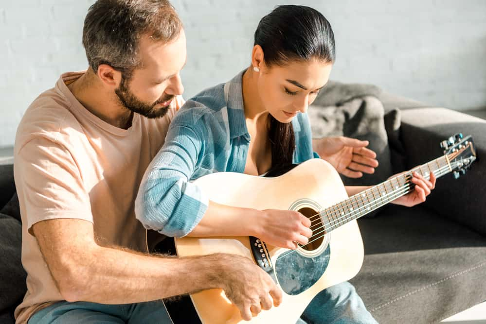 Husband teaching wife to play acoustic gutiar