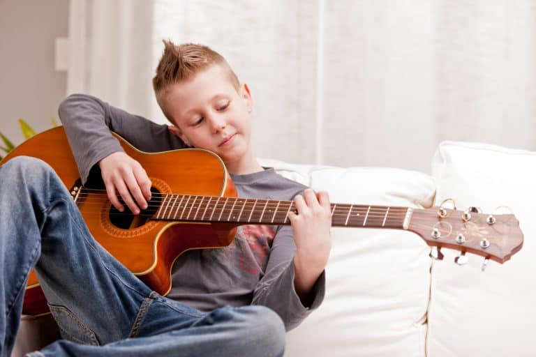 Little boy playing guitar at home