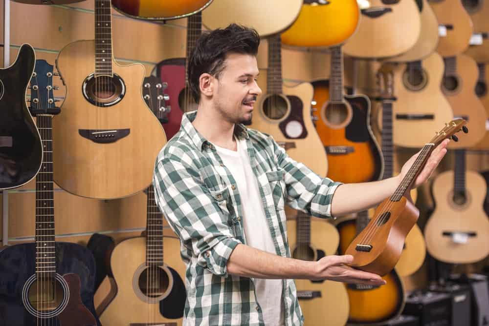 Man choosing ukulele in a music store