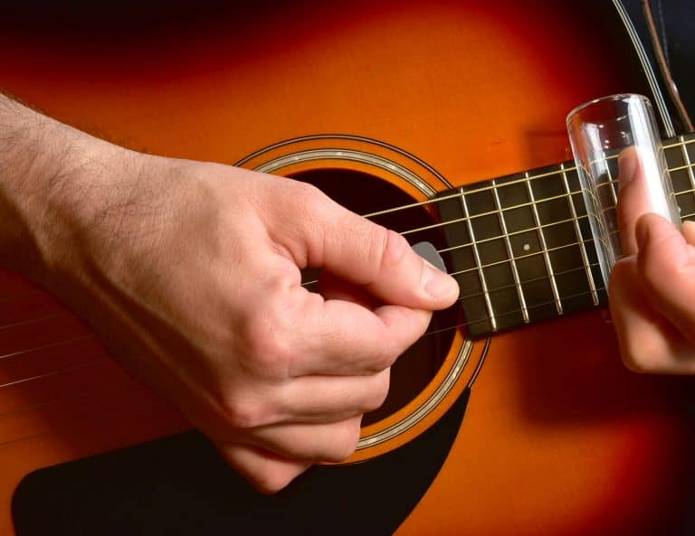 Man playing and acoustic guitar with a glass slide
