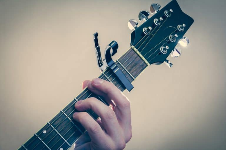 Man plays guitar with capo