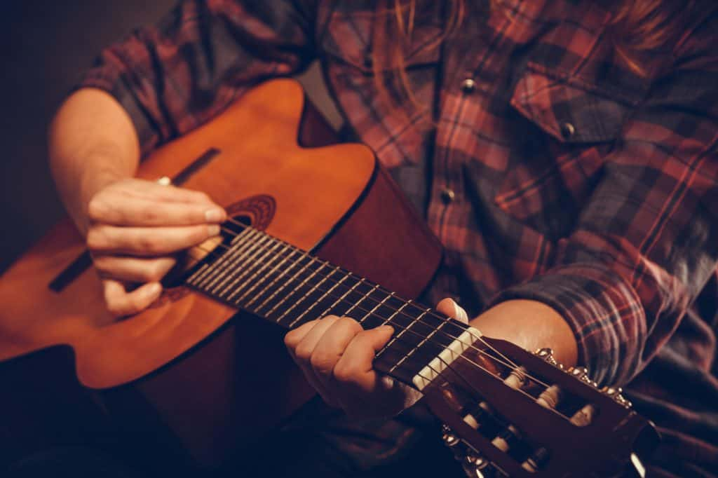 Man Strumming on Acoustic Guitar