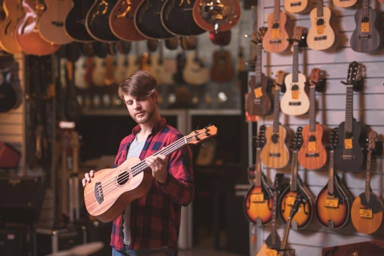 Musician with a baritone ukulele in a music store