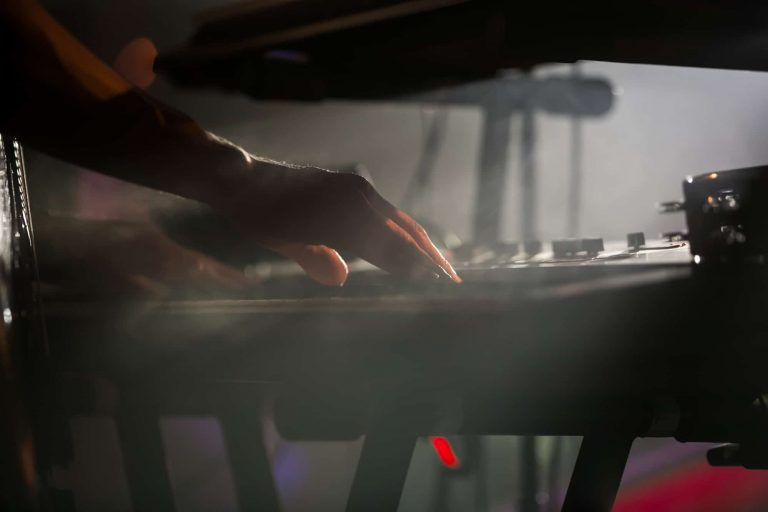 Professional pianist playing live set on stage with keyboard synthesizer