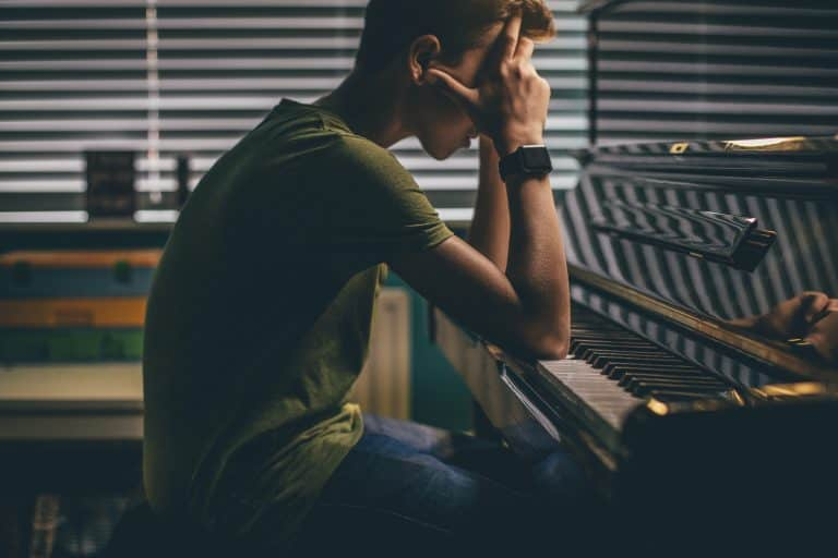Teenager sitting at his piano with his head in his hands.