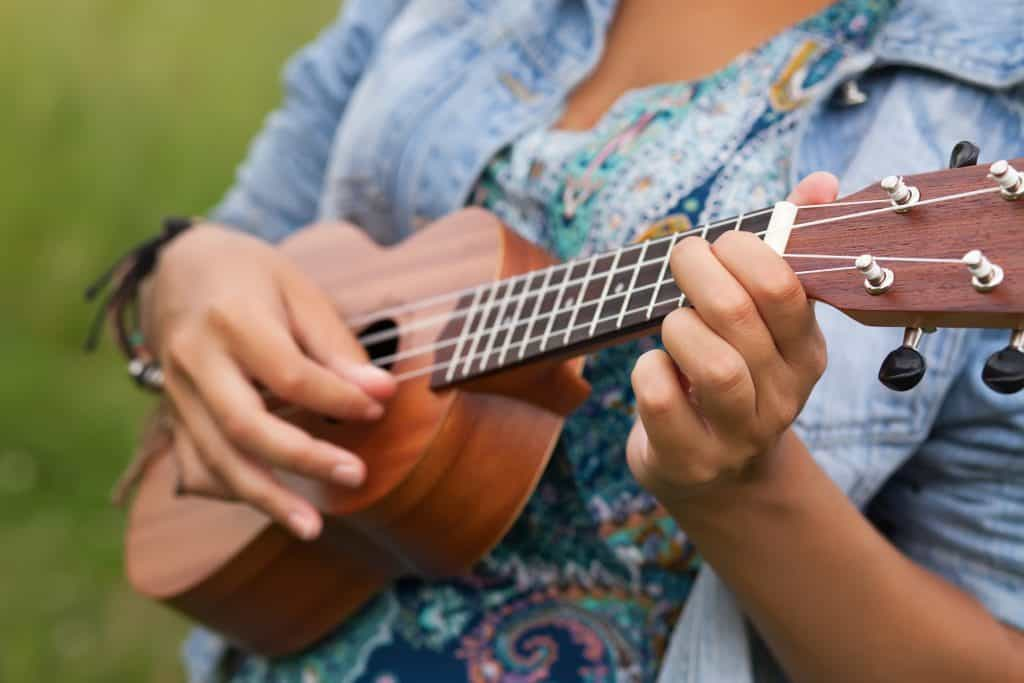 Woman playing on Ukulele outdoors