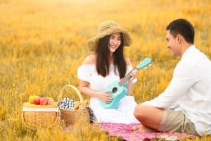 Young asian couple playing ukulele during a picnic