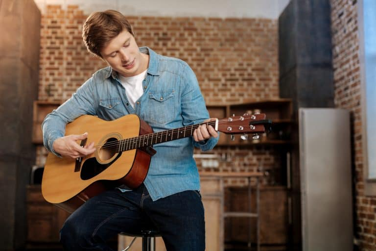Young man sitting on a stool and playing a guitar